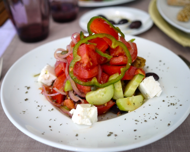 Greek salad with tomato, cucumber, sweet green peppers, red onion, Feta cheese, Kalamata olives, caper berries and barley bread