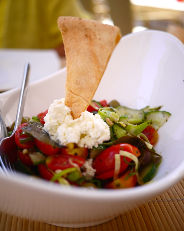 Santorini Salad with cherry tomatoes, fava, peas, zucchini, caper leaves, and galotyri cheese