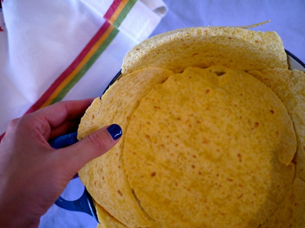 Step 2: Line the dish with corn tortillas, cutting them in half to cover the sides, letting them hang over the edge a little bit.